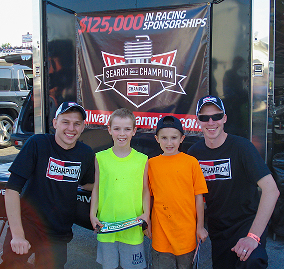 Corey and Kyle Michalek pose with two future racers at the 2013 Cavalcade of Stars race at Summit Racing Equipment Motorsports Park in Norwalk, Ohio