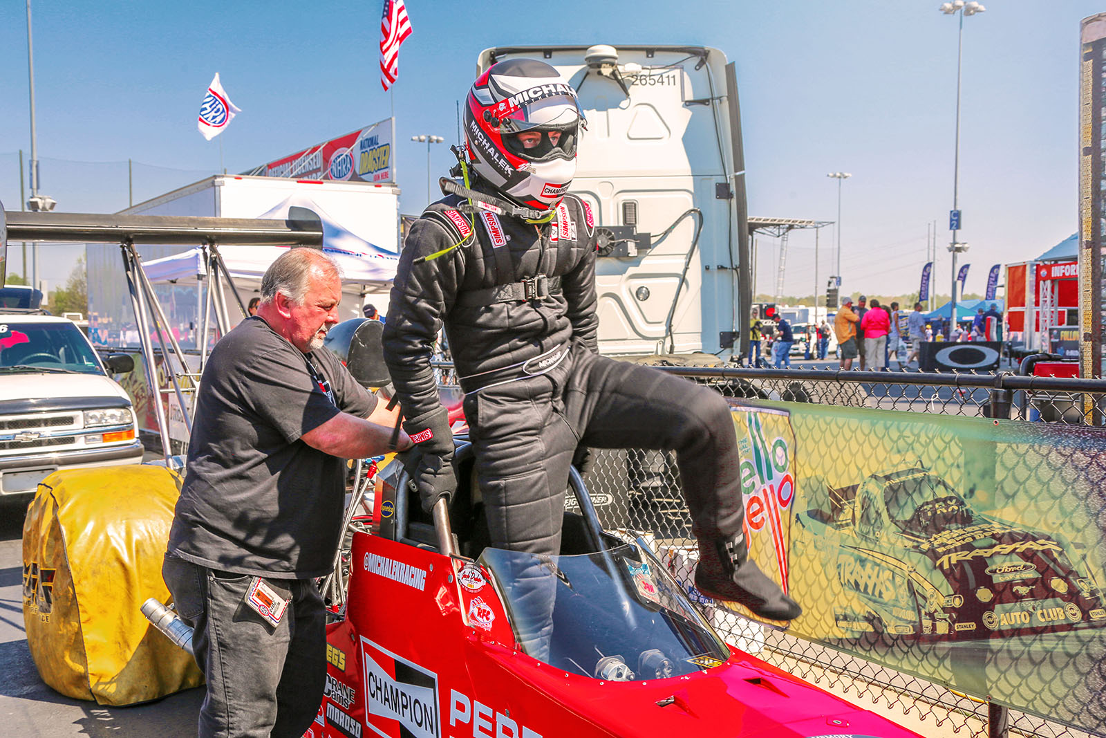 Corey Michalek climbs into the Champion Spark Plugs A/fuel dragster prior to the final round of qualifying at the 2014 NHRA Four Wide Nationals.